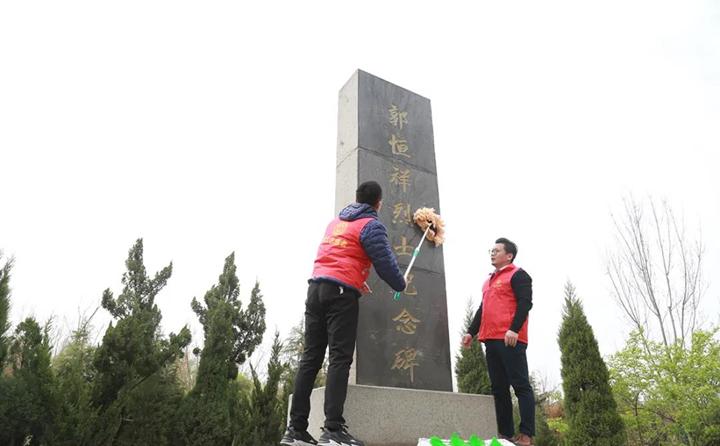 职工志愿者对纪念碑进行清理、擦拭.jpg